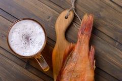 与鱼的特写镜头新鲜的啤酒在木桌上在客栈 库存照片
