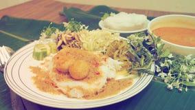 与鱼的米细面条用咖哩粉调制sace,并且菜泰国食物浸泡 免版税图库摄影
