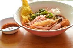 与鱼的米细面条排行和在红色汤的猪血 免版税库存照片