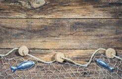 与鱼装饰的捕鱼网在棕色木背景 免版税库存照片