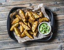 与鲕梨辣调味汁的烤香料土豆在木背景,顶视图 可口快餐或开胃菜 免版税图库摄影