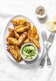 与鲕梨辣调味汁的烤香料土豆在轻的背景,顶视图 鲜美快餐、塔帕纤维布或者开胃菜 素食食物 免版税库存图片