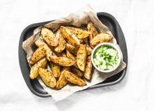 与鲕梨辣调味汁的被烘烤的土豆在轻的背景,顶视图 可口快餐或开胃菜 图库摄影