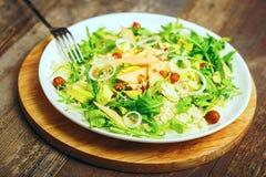 与鲕梨rucola坚果和蒸丸子素食健康食物的蔬菜沙拉 免版税图库摄影