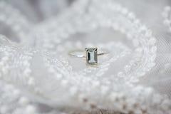 与鲜绿色被切开的蓝绿色宝石a的婚姻的定婚戒指 免版税库存图片