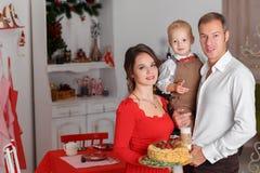 与鲜美圣诞节蛋糕的愉快的家庭在背景厨房 图库摄影
