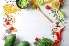 与鲜美鳄梨调味酱捣碎的鳄梨酱的构成和在木背景,顶视图的不同的产品 免版税库存照片