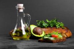 与鳄梨调味酱捣碎的鳄梨酱、沙拉和蕃茄的多士 与一个瓶子的鲕梨油、面包和绿色在桌背景 复制空间 图库摄影
