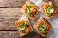 与鳄梨调味酱捣碎的鳄梨酱、虾和石灰特写镜头的可口三明治 库存照片