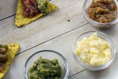 与鳄梨调味酱捣碎的鳄梨酱和辣调味汁垂度的玉米片 库存图片