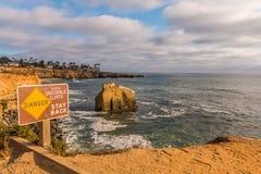 与鸟岩石的危险标志在日落峭壁 库存照片