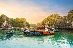 与鸟飞行的五颜六色的天空在浮动村庄在下龙湾下,越南石灰石峭壁的海  库存图片