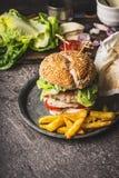 与鸡、莴苣、无盐干酪和蕃茄的自创鲜美汉堡服务用在土气厨房用桌bac的炸薯条土豆 免版税库存图片