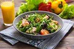 与鸡、蕃茄、芝麻菜、mesclun、蓬蒿和橙汁的新鲜的沙拉在一块布料餐巾,在木桌上 库存图片