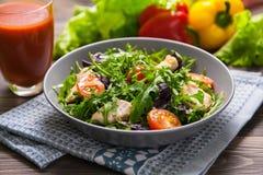 与鸡、蕃茄、芝麻菜、mesclun、蓬蒿和西红柿汁的新鲜的沙拉在一块布料餐巾,在木桌上 免版税库存照片