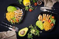 与鸡、蕃茄、鲕梨、莴苣和扁豆的健康盘在黑暗的背景 正餐 免版税库存图片