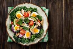 与鸡、蕃茄、鸡蛋和莴苣的新鲜的沙拉在板材 库存照片