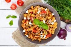 与鸡、蘑菇、西红柿、希腊白软干酪和西红柿酱的面团Radiatori在白色木背景 免版税库存图片