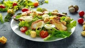 与鸡、蛋鹌鹑、蕃茄、乳酪和油煎方型小面包片的新鲜的健康凯萨色拉在一块白色板材 图库摄影