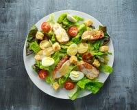 与鸡、蛋鹌鹑、蕃茄、乳酪和油煎方型小面包片的新鲜的健康凯萨色拉在一块白色板材 免版税库存图片