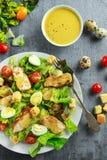 与鸡、蛋鹌鹑、蕃茄、乳酪和油煎方型小面包片的新鲜的健康凯萨色拉在一块白色板材 免版税库存照片