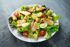与鸡、蛋鹌鹑、蕃茄、乳酪和油煎方型小面包片的新鲜的健康凯萨色拉在一块白色板材 库存照片