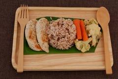 与鸡内圆角格栅服务的ฺBrown米用煮沸花椰菜和红萝卜 免版税库存照片