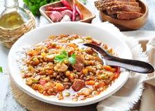 与鸡和意大利辣味香肠香肠、葱、红萝卜、甜椒、大蒜和荷兰芹的扁豆汤 免版税图库摄影