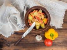 与鸡和红辣椒的被烘烤的土豆 大蒜,蕃茄,黄色胡椒,顶视图 在陶瓷碗和刀子的烘烤 免版税库存图片