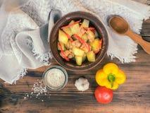 与鸡和红辣椒的被烘烤的土豆 盐、大蒜、蕃茄和黄色胡椒,顶视图 在陶瓷碗的烘烤 免版税库存照片