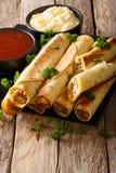 与鸡和调味汁特写镜头的墨西哥taquitos 垂直 免版税库存图片