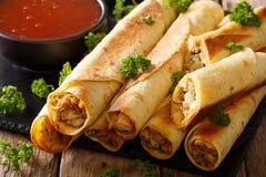 与鸡和辣味番茄酱特写镜头的墨西哥taquitos horizont 免版税库存照片