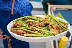 与鸡大腿的油煎的绿色芦笋,在官员的手上 用餐营养的概念 抛光 食物 库存图片
