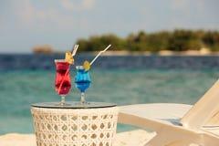 与鸡尾酒的两块玻璃在海滩长凳或轻便折叠躺椅附近的桌与蓝色海洋和在背景的白色沙子上 库存照片