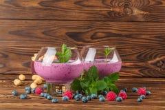 与鸡尾酒的大玻璃在木背景 开胃奶昔用蓝莓、薄菏和花生 复制空间 免版税库存照片