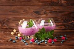 与鸡尾酒的大玻璃在木背景 开胃奶昔用蓝莓、薄菏和花生 复制空间 库存图片