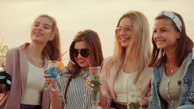 与鸡尾酒的女孩白种人出现身分在他的在房子的高屋顶的手上反对城市的 股票录像