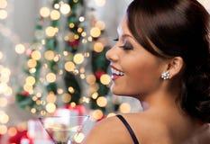与鸡尾酒的妇女面孔在圣诞灯 库存照片
