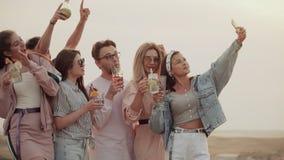 与鸡尾酒的快乐的公司在他们的手上,微笑的摆在照相机智能手机的 夏天都市鸡尾酒 股票录像