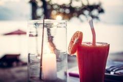 与鸡尾酒的被弄脏的海滩假日在玻璃的背景和蜡烛在日落海滩caffe 库存图片