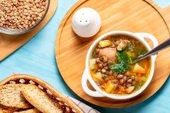 与鸡的扁豆汤在一个木板在一张蓝色桌上,顶视图的一个白色碗 库存图片