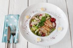 与鸡的温暖的在白色木头的沙拉和多士 免版税库存图片