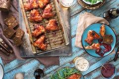 与鸡翼和啤酒,土气样式的饭桌 库存照片
