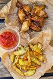 与鸡翼和鼓槌的被烘烤的炸薯条 免版税库存照片