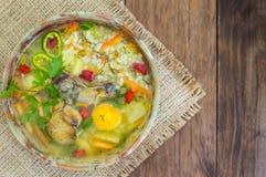 与鸡肚脐和蛋黄的米汤 背景土气木 顶视图 特写镜头 库存图片