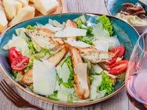 与鸡胸脯、帕尔马干酪、油煎方型小面包片、蕃茄、混杂的绿色、莴苣和杯的沙拉在木背景的酒 库存照片