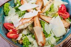 与鸡胸脯、帕尔马干酪、油煎方型小面包片、蕃茄、混杂的绿色、莴苣和杯的沙拉在轻的木背景的酒 库存图片