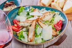 与鸡胸脯、帕尔马干酪、油煎方型小面包片、蕃茄、混杂的绿色、莴苣和杯的沙拉酒 库存照片