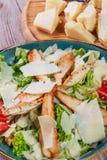 与鸡胸脯、帕尔马干酪、油煎方型小面包片、蕃茄、混杂的绿色、莴苣和杯的沙拉酒 免版税库存照片