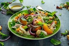 与鸡胸脯、桃子、红洋葱、油煎方型小面包片和菜的新鲜的沙拉在一块绿色板材 健康的食物 库存照片